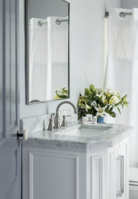 White sink with carrera marble top and white flowers