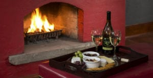 A tray of cheese and crackers and a bottle of wine, set in front of a blazing fire