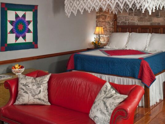 A red leather sofa in the foreground and a hand-carved king bed with lace canopy in the background
