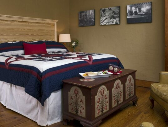 Queen bed with blue canopy and hand sewn Amish quilt.