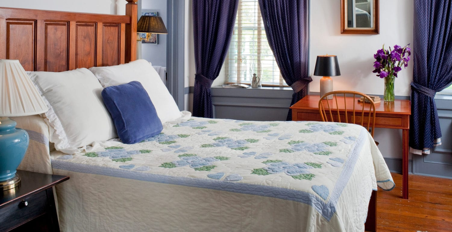 A Blue hand-sewn Amish quilt sits atop this queen sized, hand-carved bed.
