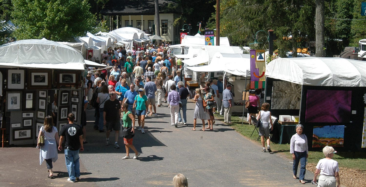 A crowd of shoppers walk the path between the white vendor tents and tall trees at the Mt Gretna Arts Festival
