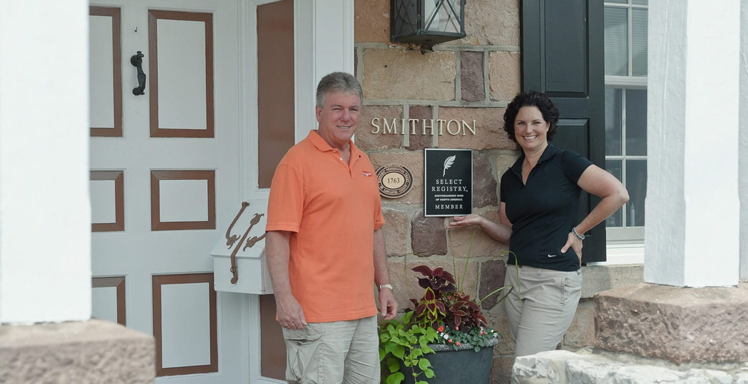 Innkeepers at their white front door in front of the historic stone B&B