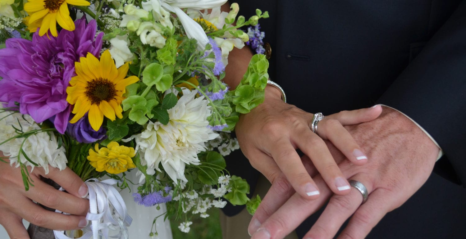 A bride and groom show their wedding rings as bride holds bouquet of white, green yellow and purple wild flowers.