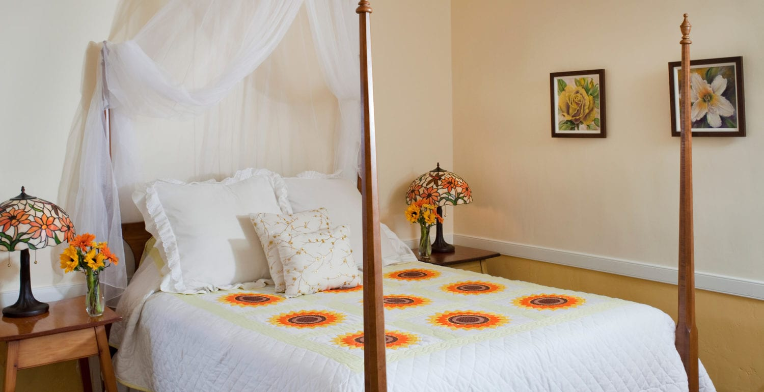 Four poster queen sized bed with hand sewn Amish sunflower quilt and yellow toned Tiffany lamps.