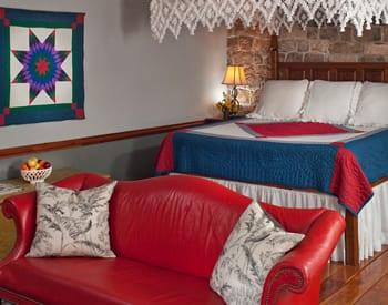 View of the bed and sofa in the Crimson Dove Suite