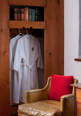 Two white, embroidered, spa bathrobes are hanging in the closet