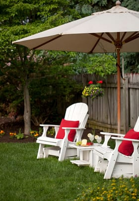 Two white gliding chairs with red pillows in the back garden