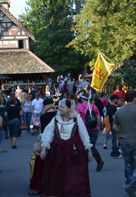 A large crowd enjoys the PA Renaissance Faire with yellow and red flag in the background