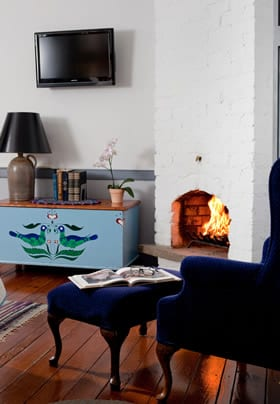 A fire is lit. On the right is a blue wingback chair, and on the left is a painted chest