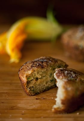 Zucchini muffin on a wood surface with yellow zucchini flower in the background