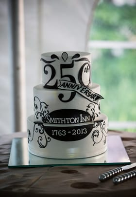 A brown and white three tiered cake celebrating the B&Bs 250th Anniversary