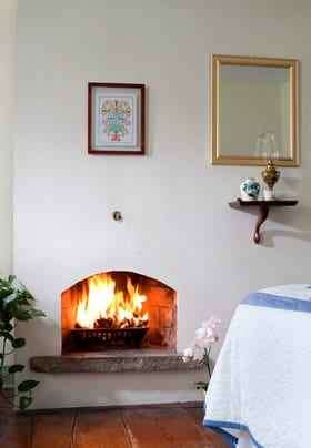 A charming fireplace with red blazing fire at the foot of the bed